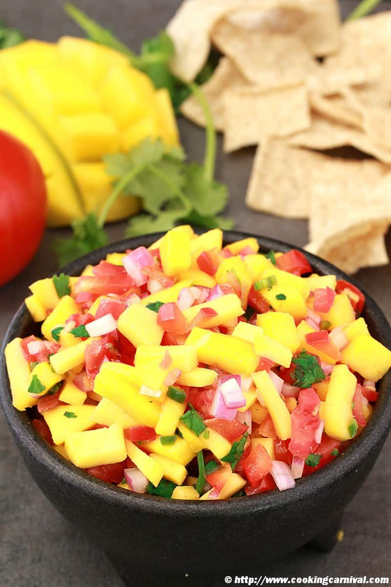 mango salsa in a black bowl with tortilla chips on the side