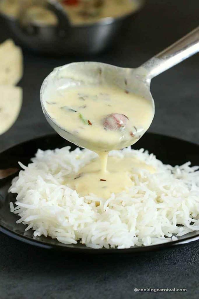 Pouring gujarati kadhi over basmati rice