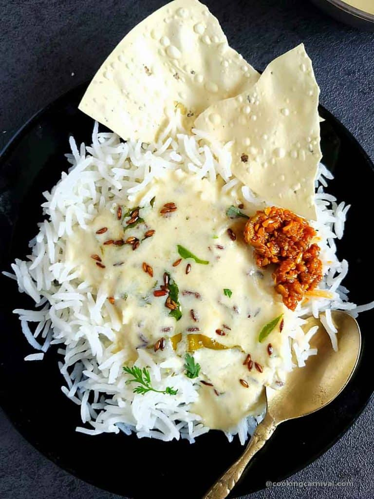 Kadhi bhat, pickle and papad in a black plate
