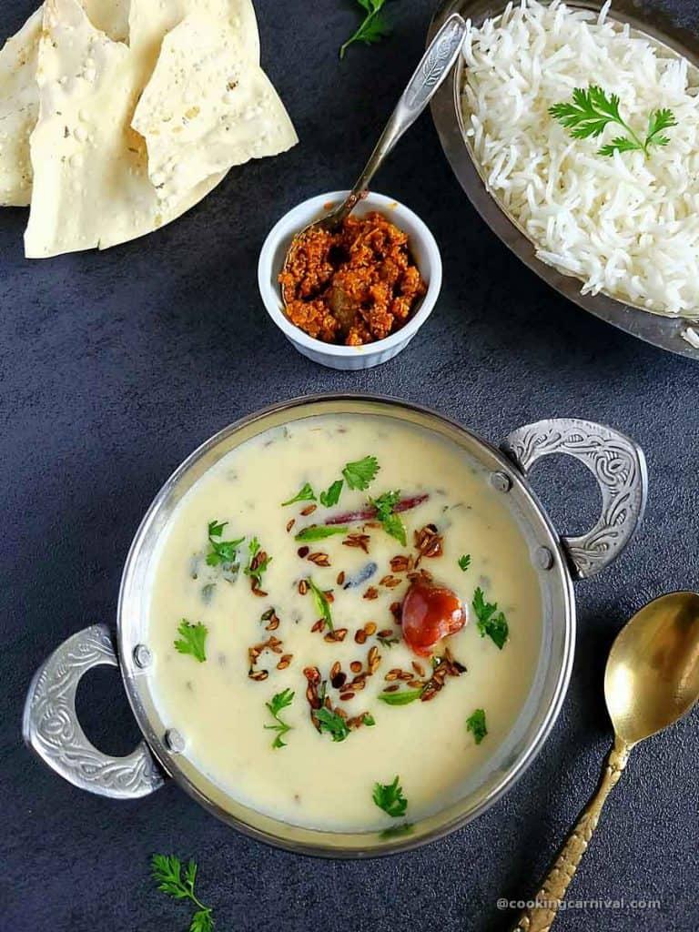 Gujarati kadhiin steel bowl, rice, pickle and papad on sides