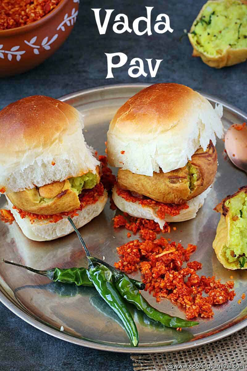 2 vada pav in a steel plate with fried green chilies and dry garlic chutney on the side