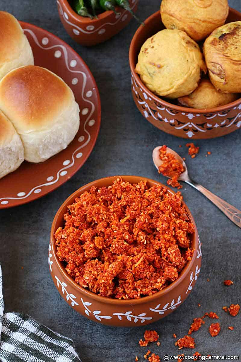 dry garlic chutney served in a traditional ware, pav and vada on the sides