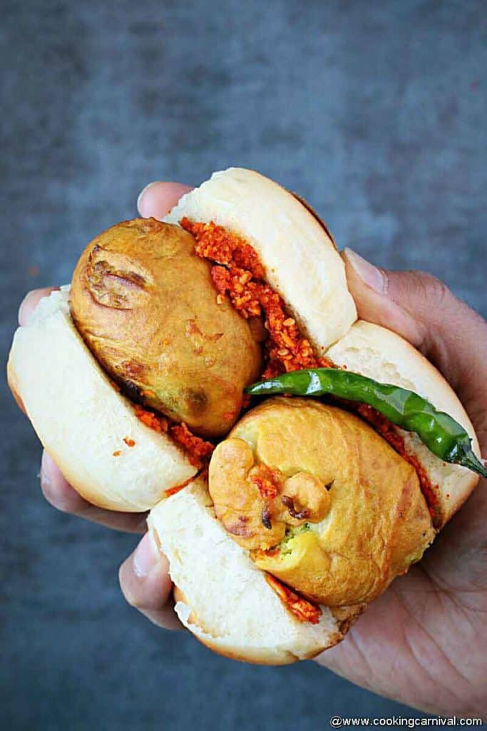 holding 2 vada pav with fried green chilies
