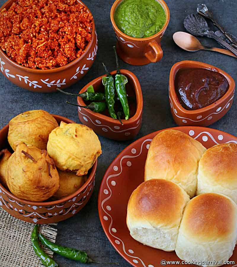 vada, bun, green fried chilies, sweet chutney, green chutney, dry garlic chutney served in a indian traditional serving ware