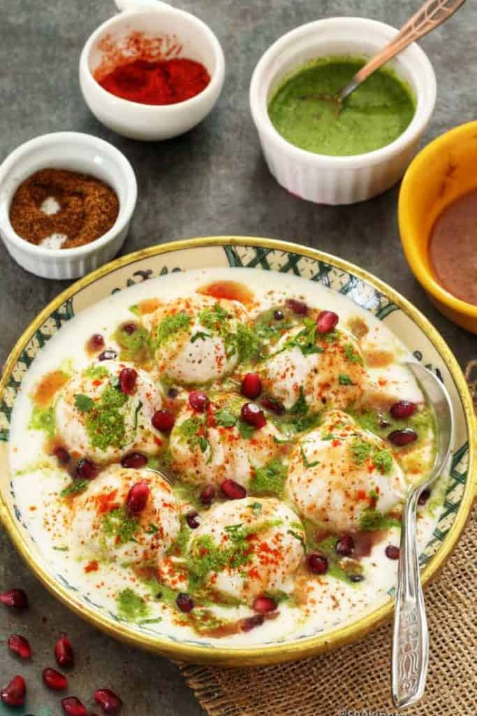 Dahi vada in a bowl, condiments on the sides