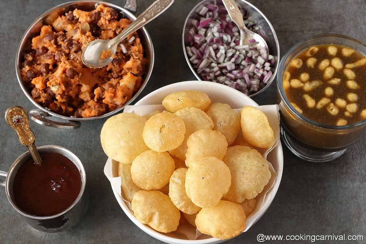 Puri, sweetchutney, stuffing, chopped onion, teekha pani on a black tile