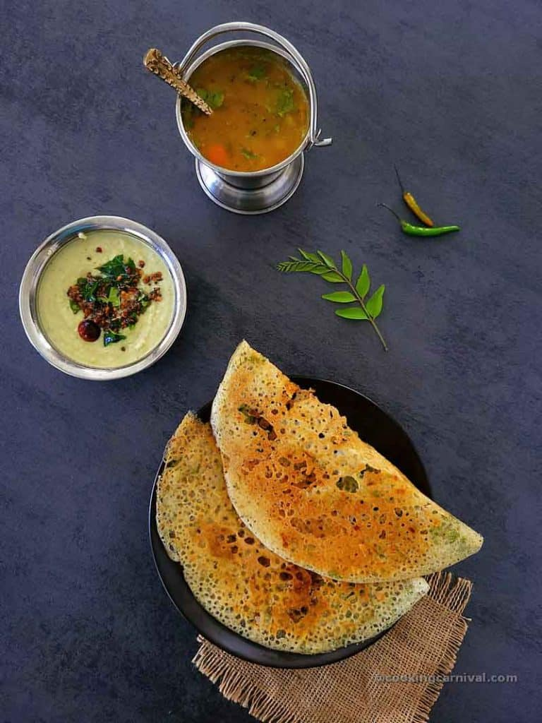 2 Rava dosa in a black plate, coconut chutney and sambar on the side