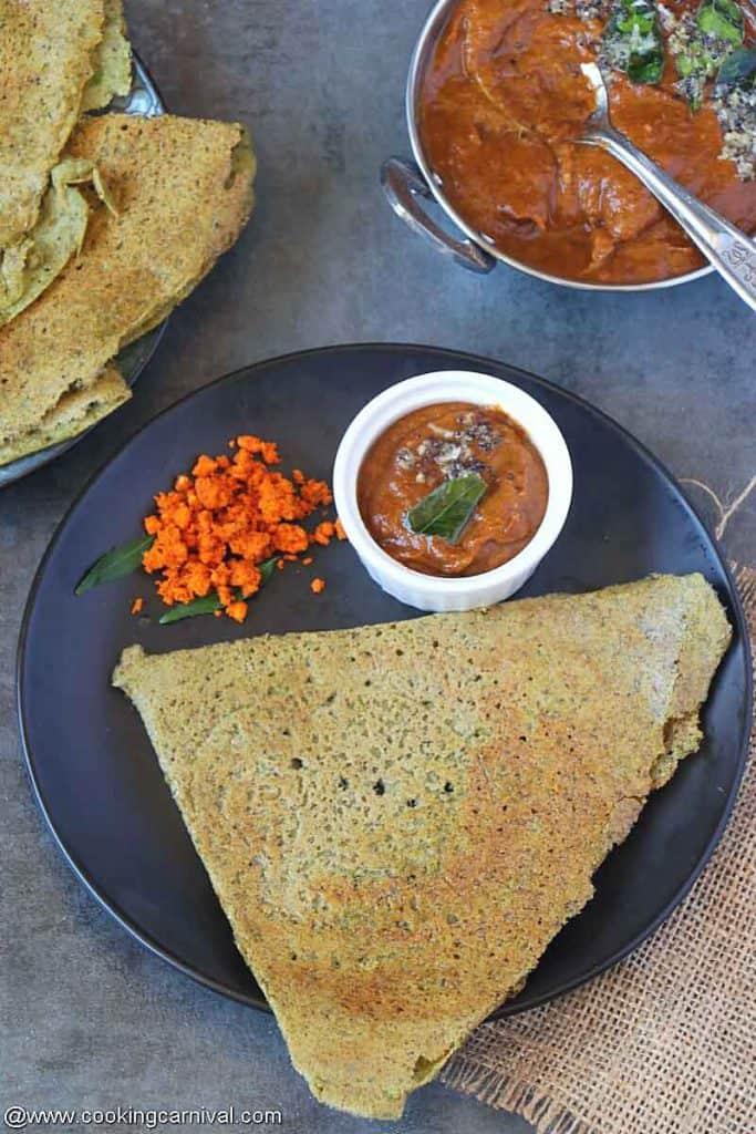 Pesarattu, allam pachadi and peanut powder on a black plate
