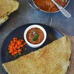 Pesarattu in black plate with ginger chutney and peanut powder