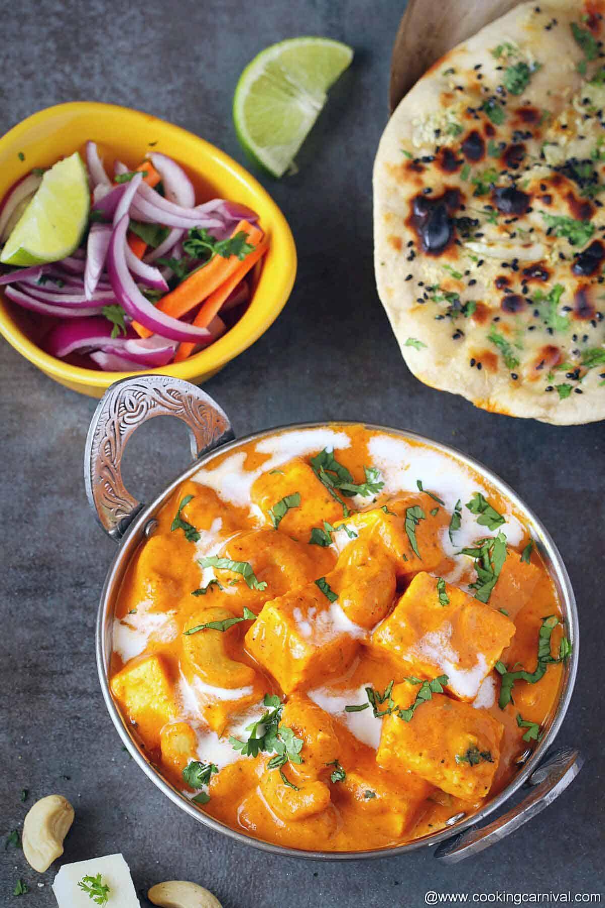 Final dish shot of paneer curry, tandoori roti and onion salad on the side