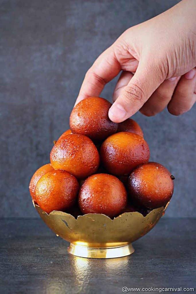 Picking up gulab jamun from the bowl