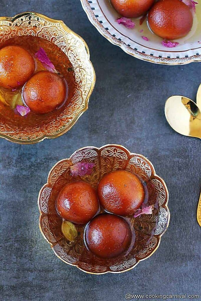 Gulab jamuns in bowls, spoons on the side