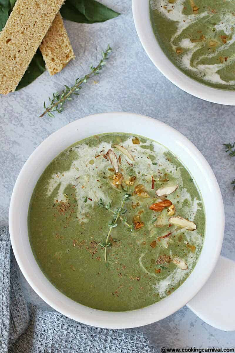 Spinach Soup in white bowl, garnished with sauteed garlic, almonds and cream