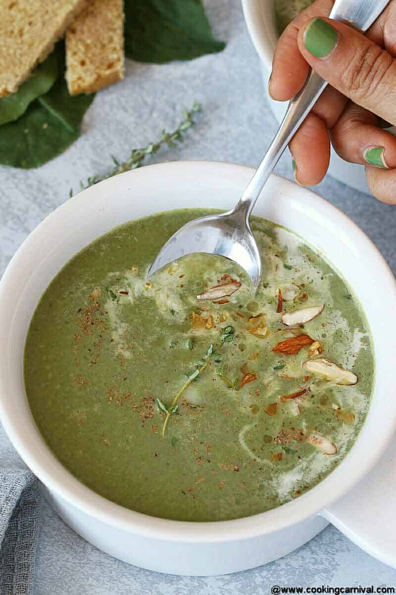 Eating Instant pot green soup with spoon from white bowl