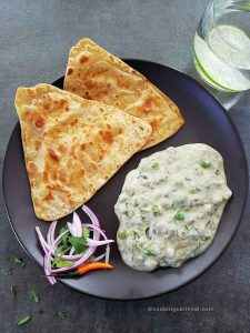 Methi matar malai with paratha and onion on a black plate