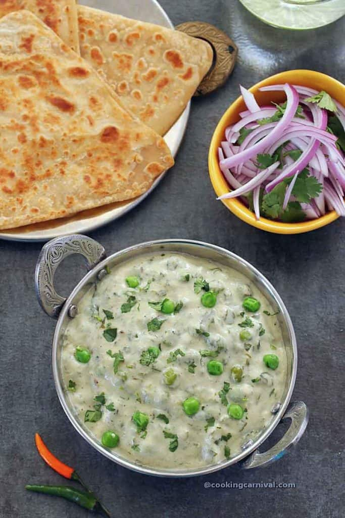 Methi matar malai in a steel bowl, plain paratha and onion on the sides
