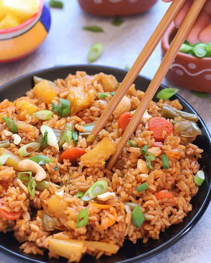 Classic and Exotic with tropical flavors - Thai Pineapple Fried Rice Recipe - Lovely blend of sweet- savory flavors and its Truly Heavenly. This Vegan Pineapple Fried rice preparation is a little bit spicy, tangy and sweet. Make it as the main course or as a side dish to any meal over the weekend. Thai Pineapple Fried rice is always a favorite.