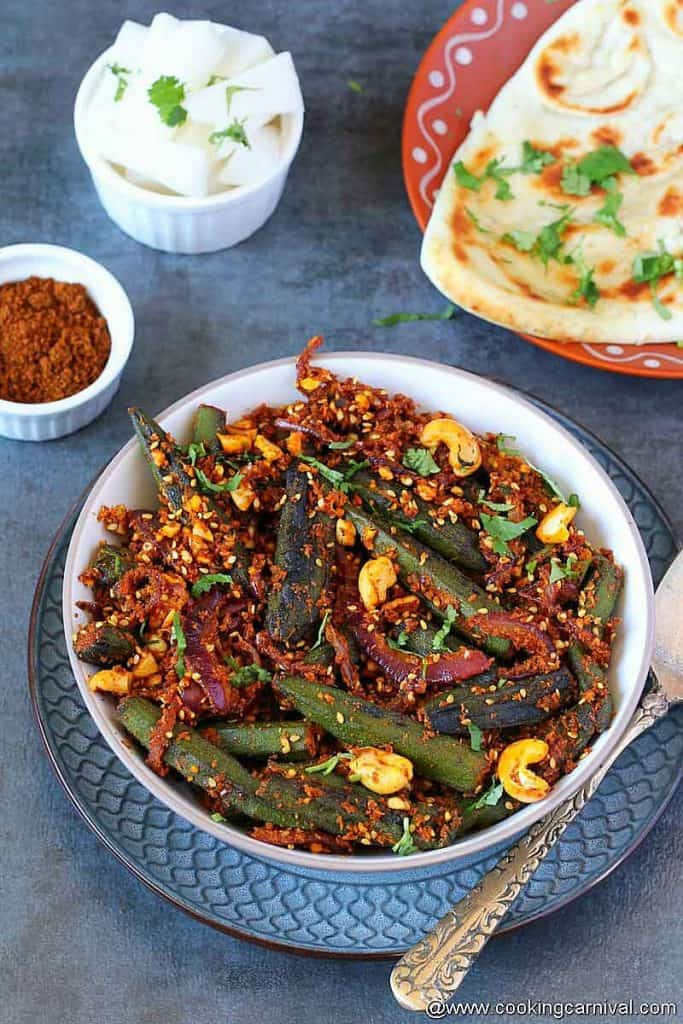 Bhindi Masala in a bowl, naan on the sides