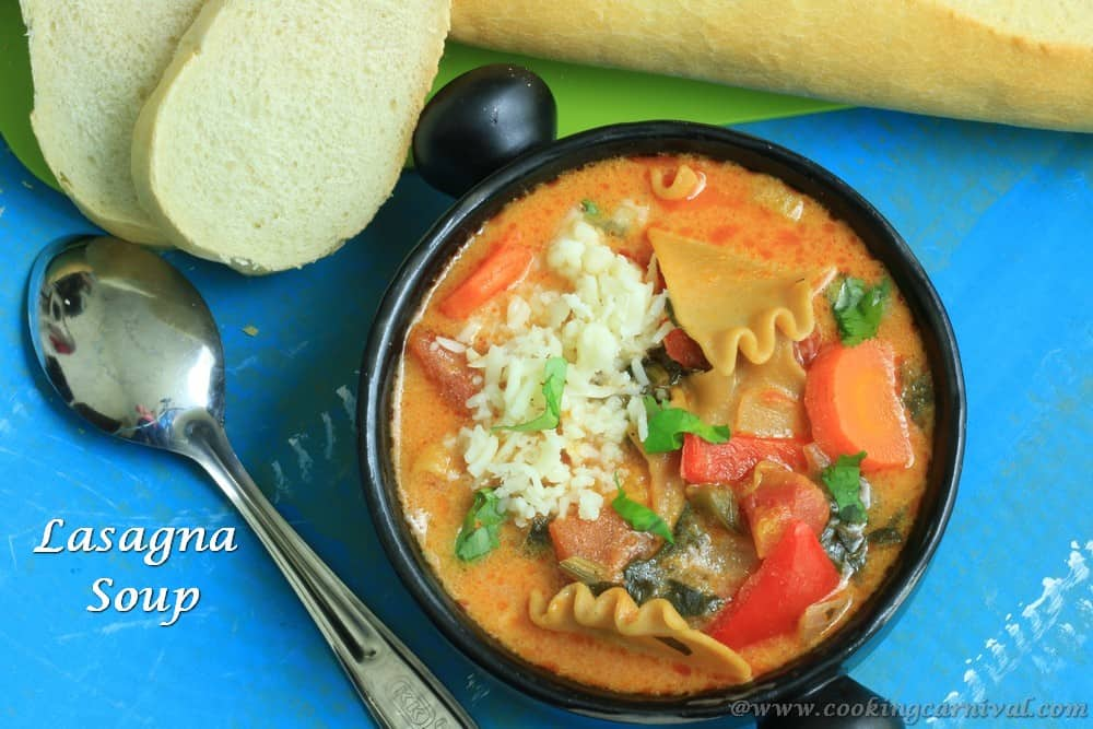 Lasagna Soup in black bowl and crusty bread on the sides