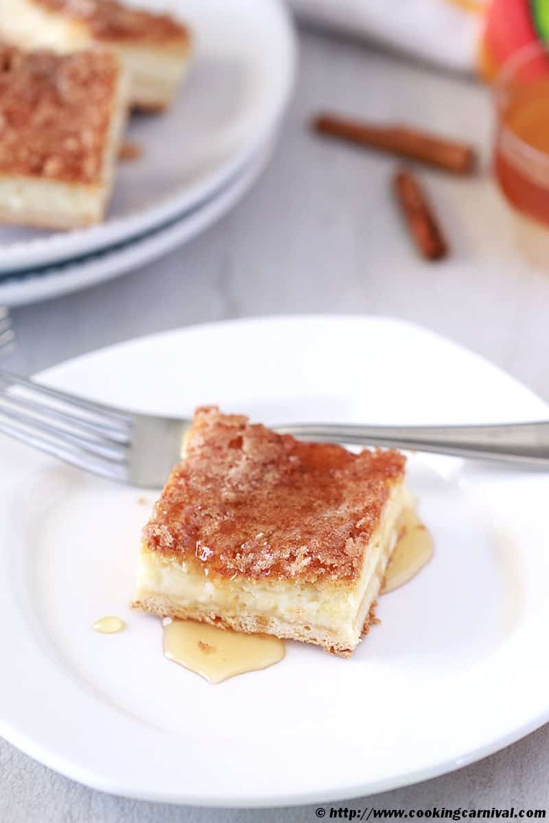 Sopapilla Cheesecake Bars with honey on white plate, fork, cinnamon sticks on the side