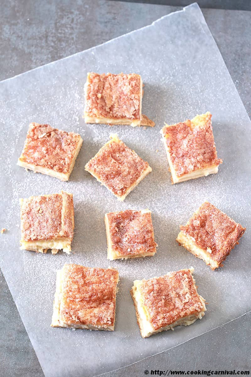 Sopapilla Cheesecake Bars on a black background with parchment paper