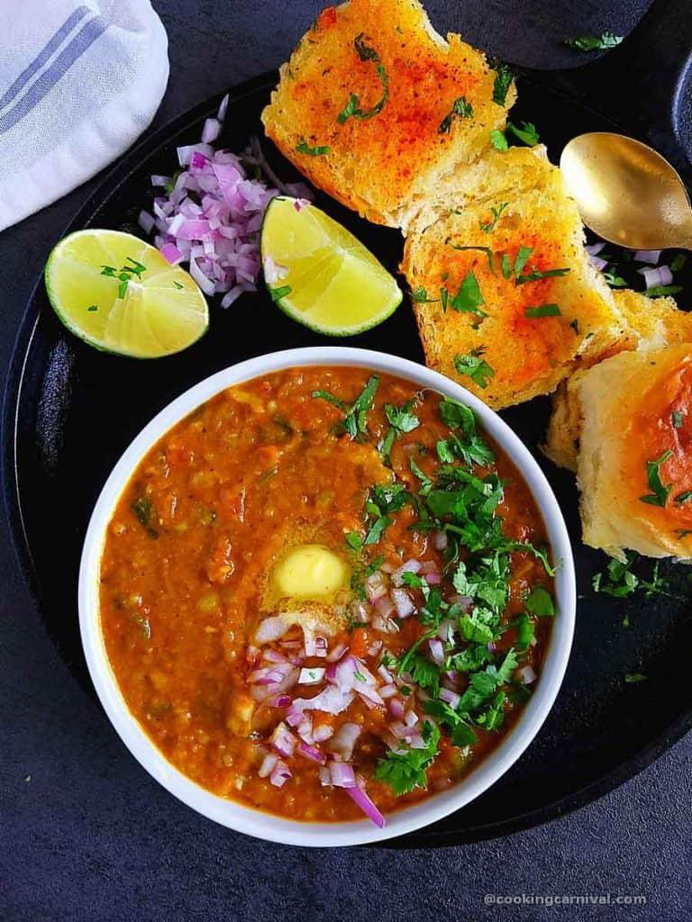 Pav bhaji in white bowl, toasted pav bread on the side