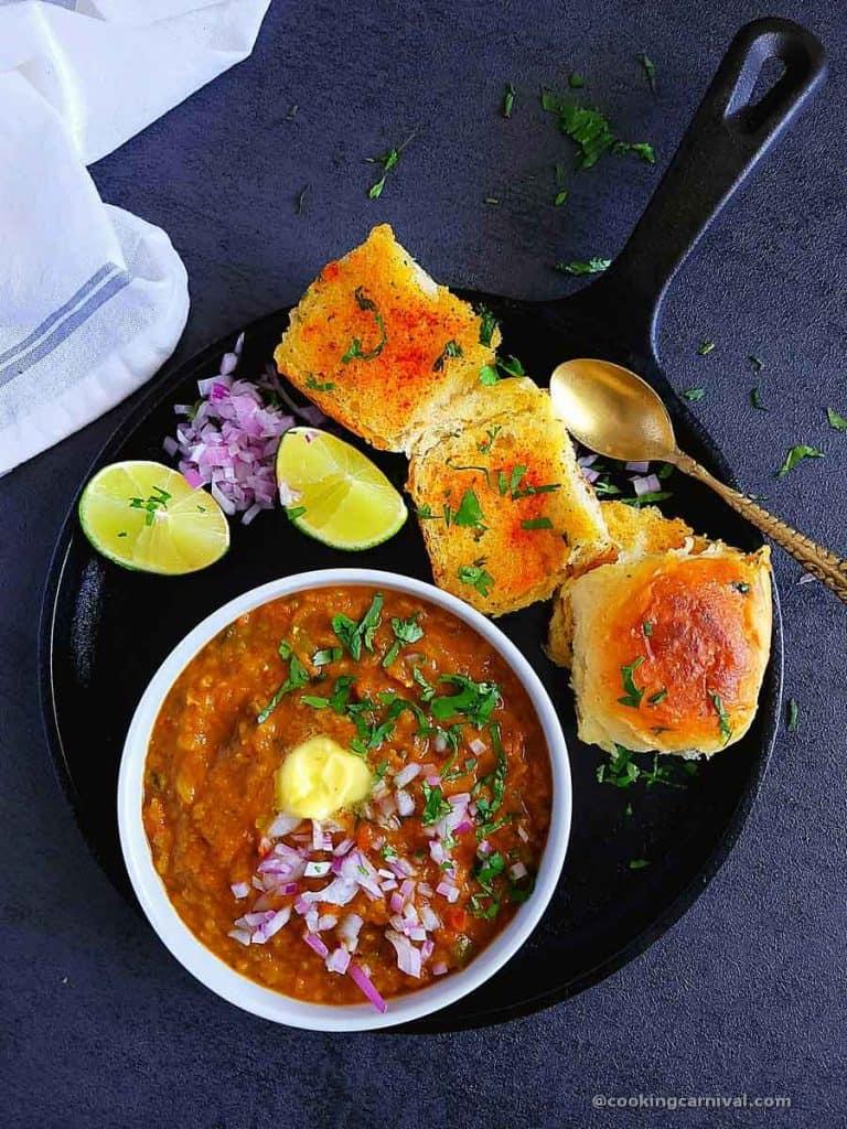 Bhaji served with pav, onion, cilantro, lemon