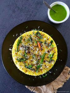Dhokla with tempering on top, green chutney on the side
