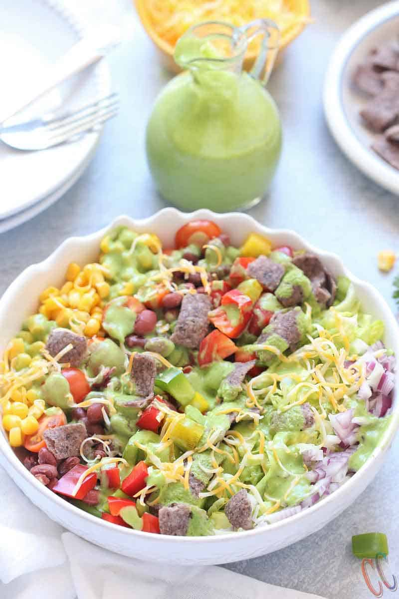 Southwest Salad - Bursting with small kidney beans, corn, bell peppers, cherry tomatoes, sweet corn, cheese, crispy lettuce, onions and bathed in Creamy-smooth Avocado Dressing, topped with blue corn tortilla chips. A super simple and classic salad that can be eaten in any season, be it summer, winter, spring or fall!