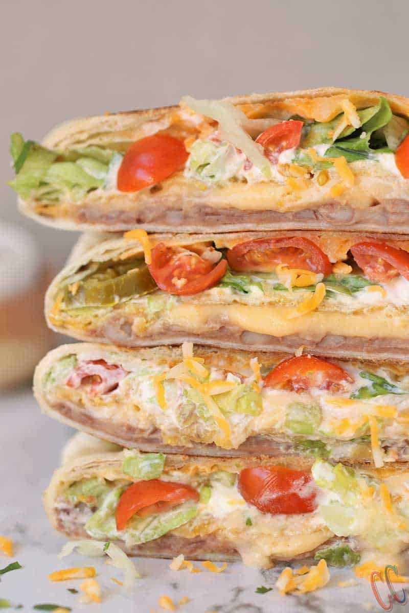 Vegetarian Homemade Crunchwrap Supreme Recipe - Refried beans, cheese sauce, crunchy tostadas, sour cream, chopped lettuce, diced tomatoes, Jalapenos and shredded cheese all wrapped inside a large burrito tortilla and then pan roasted until perfectly golden brown in color.