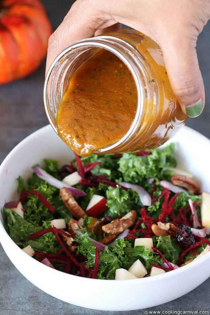 Pouring best Pumpkin Vinaigrette in autumn salad