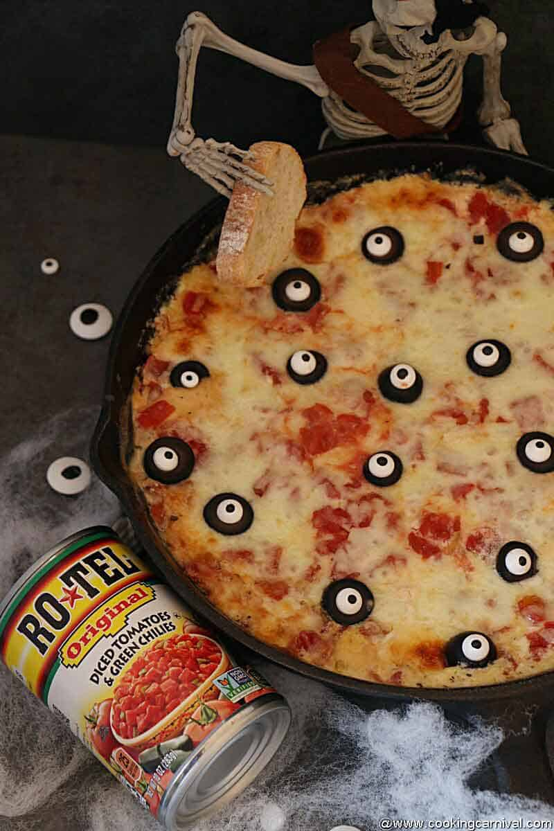 Halloween themed Pizza dip baked in a cast iron pan, Rotel tomatoes can on the sides
