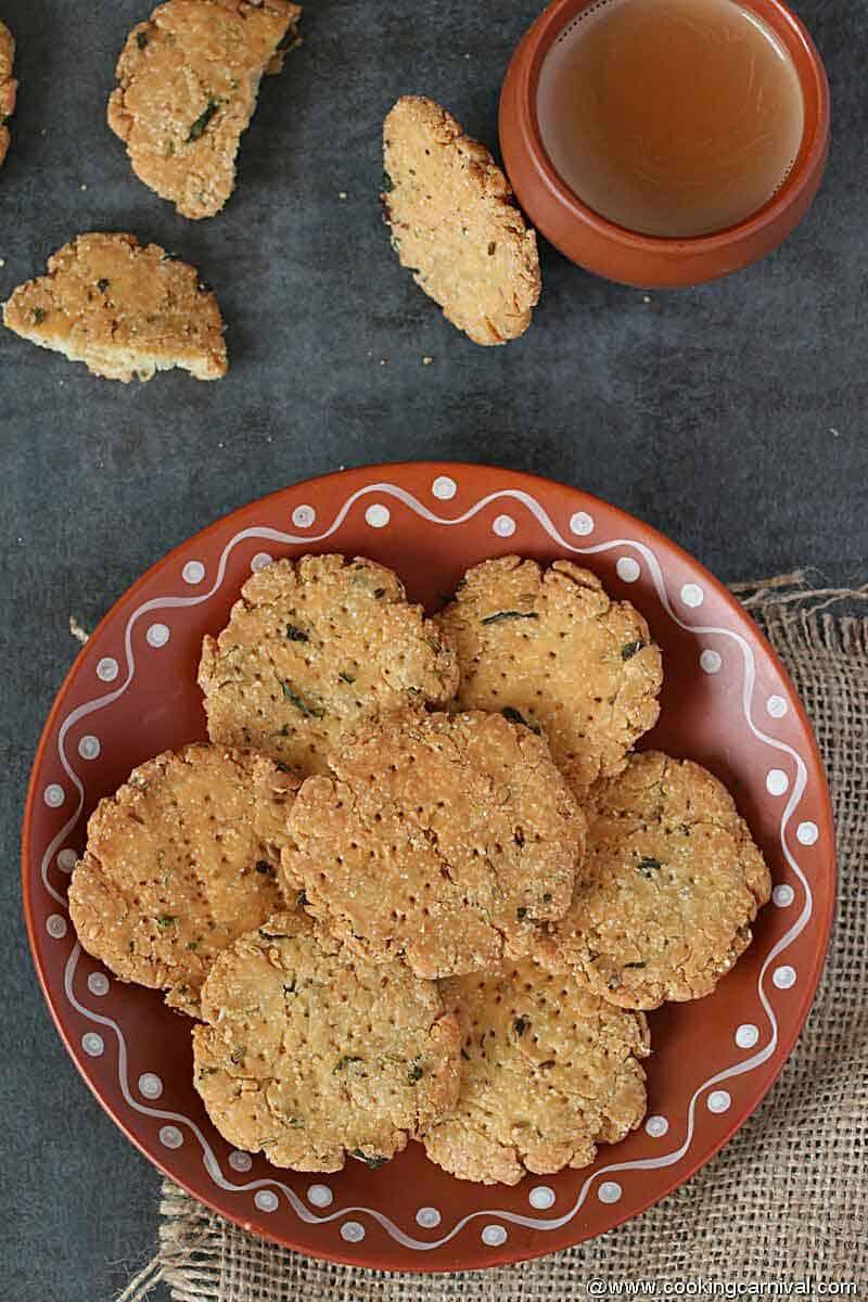 Masala methi mathri in traditional plate, masala chai on the side