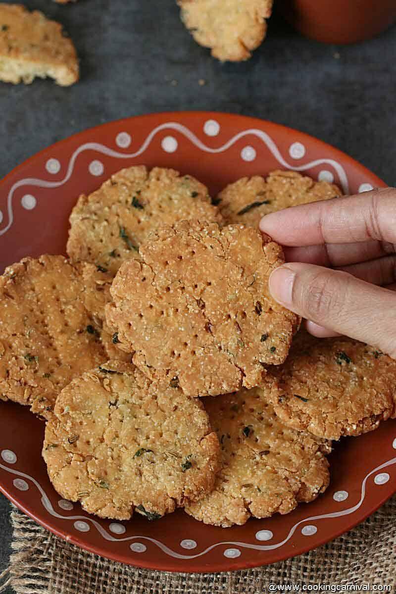 Hand picking punjabi masala methi mathri from the brown plate