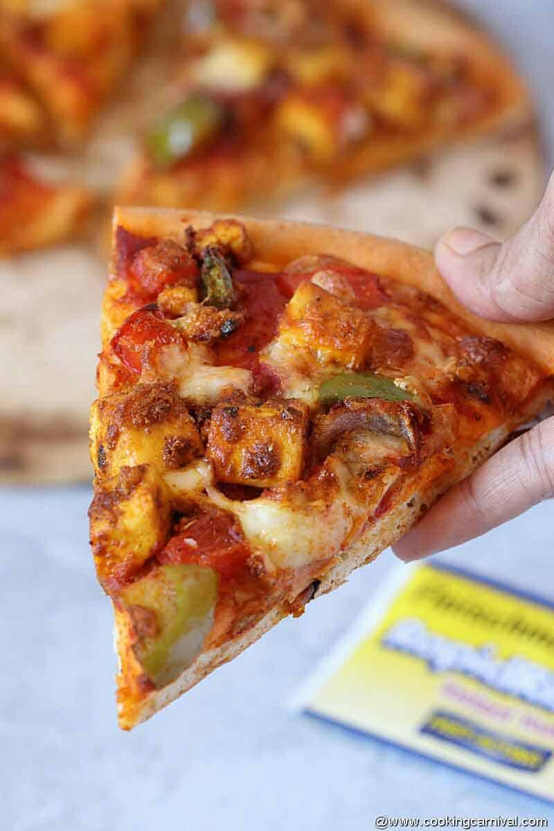 Eating slice of paneer tikka pizzza