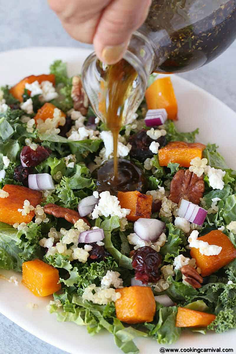 Pouring salad dressing in a roasted butternut squash and quinoa salad