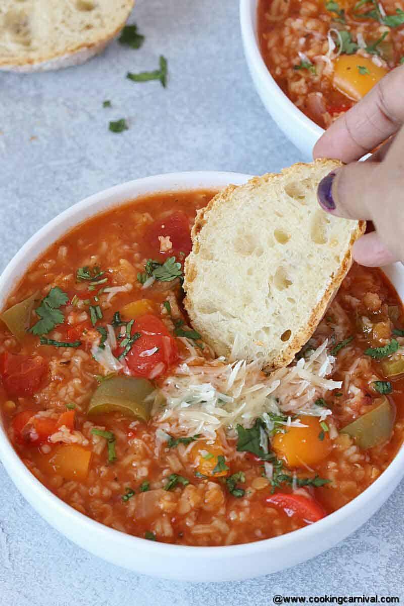 dipping crusty bread in vegetarian instant pot stuffed pepper soup