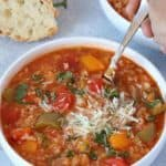 spooning vegetarian instant pot stuffed pepper soup from white bowl