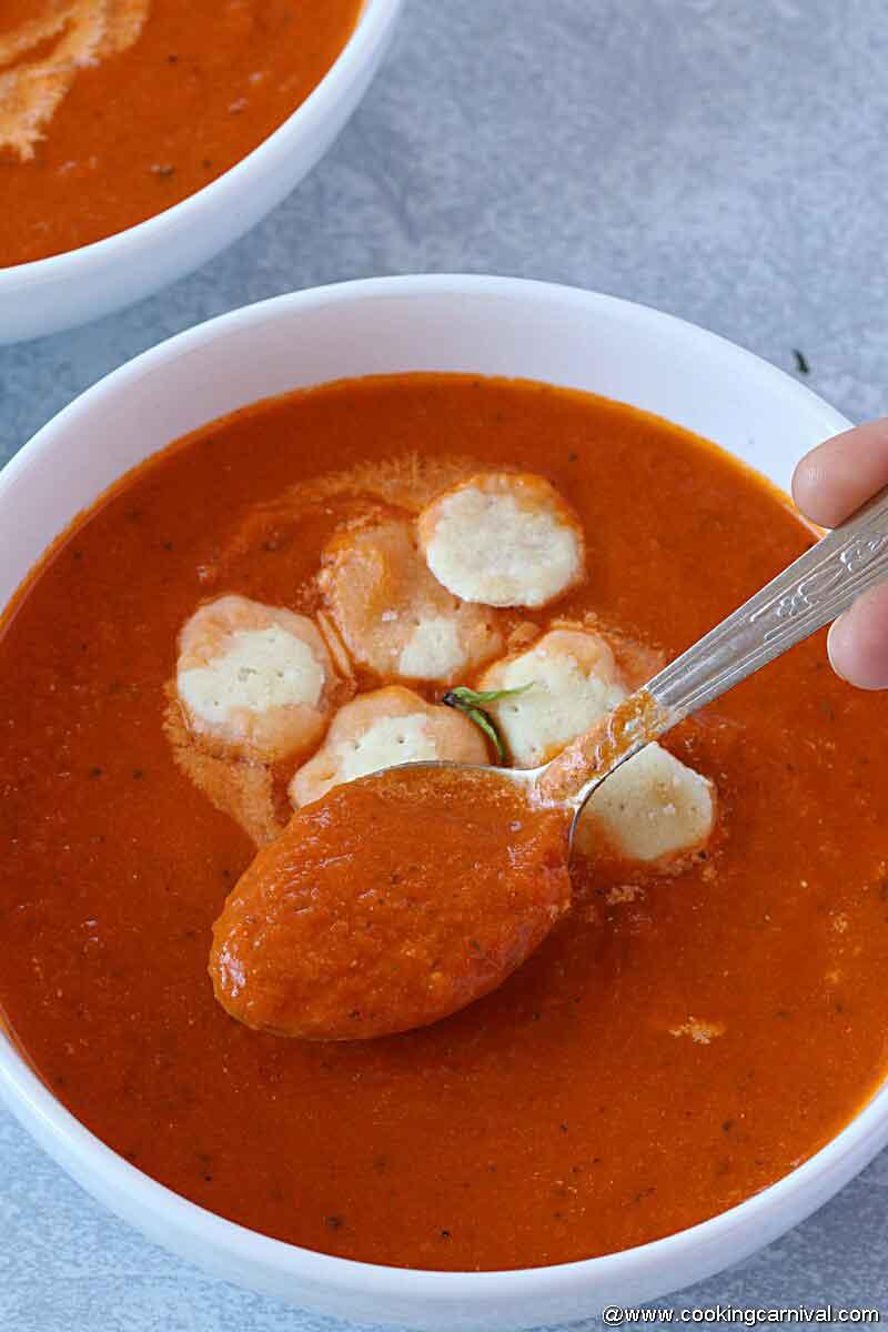 spooning tomato basil soup