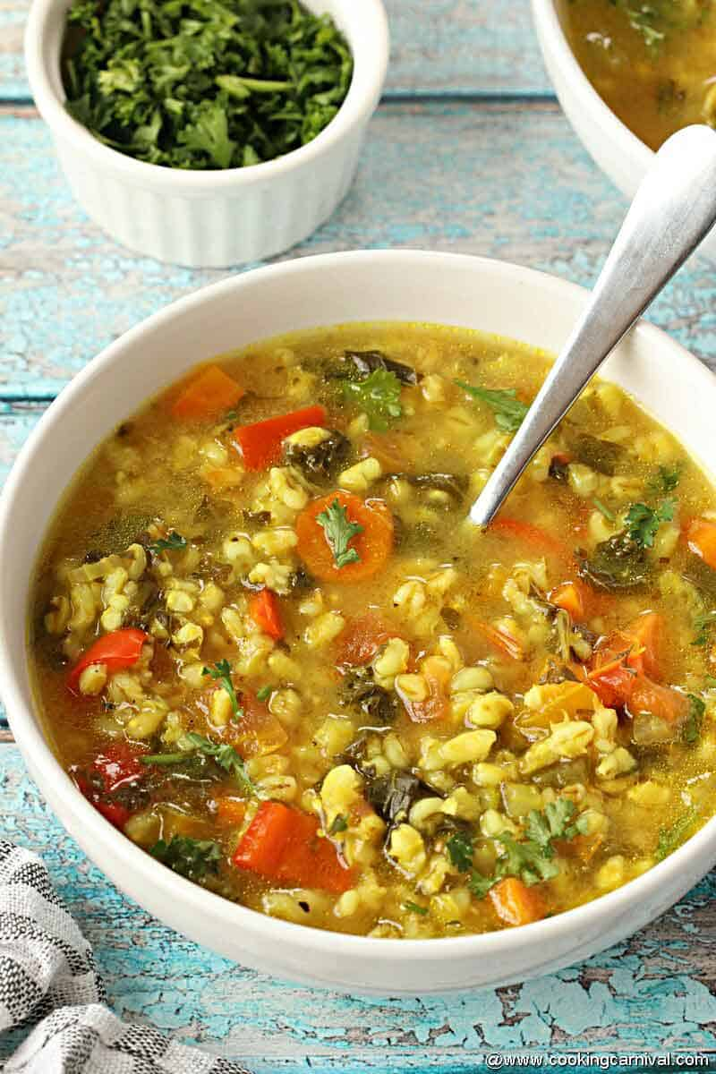 Vegetable barley Soup in white bowl with spoon