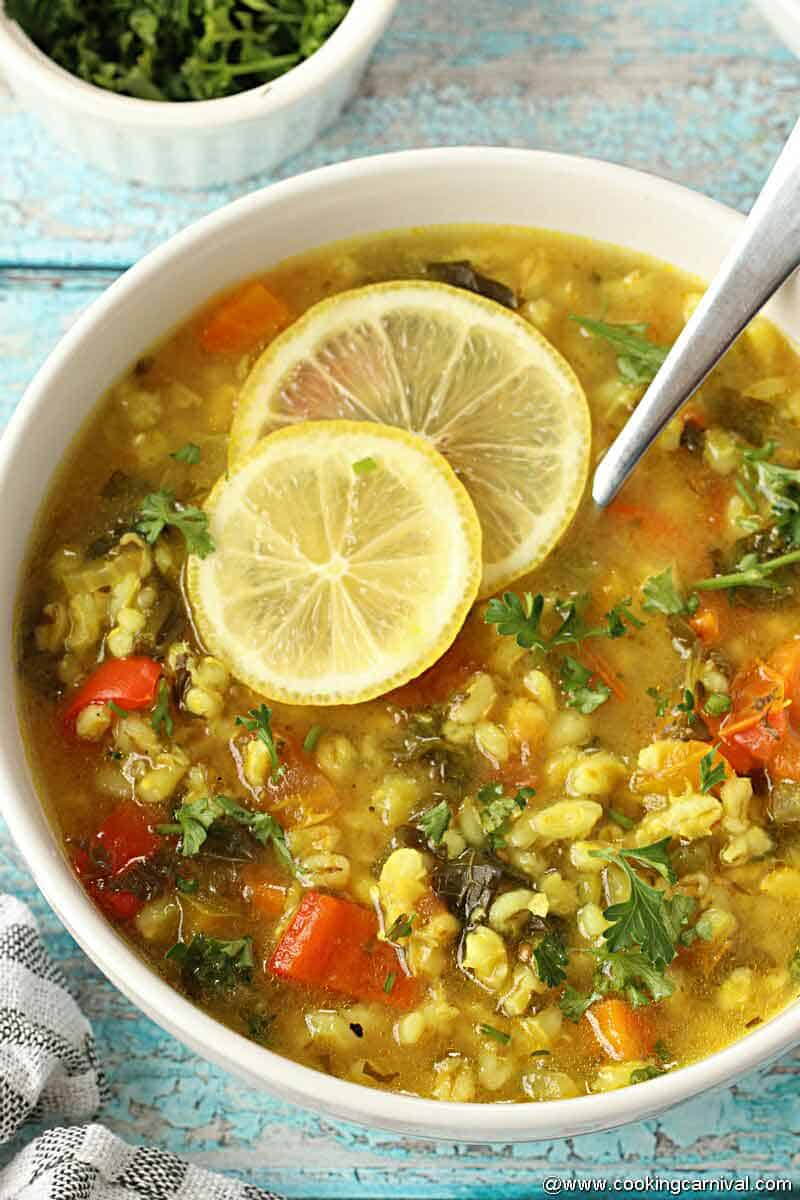 Easy vegetable barley soup in white bowl garnished with lemon slices and parsley