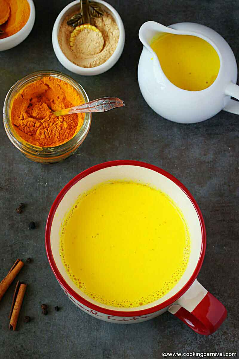 Golden milk in big wide mouth mug, turmeric, dry ginger powder on the side