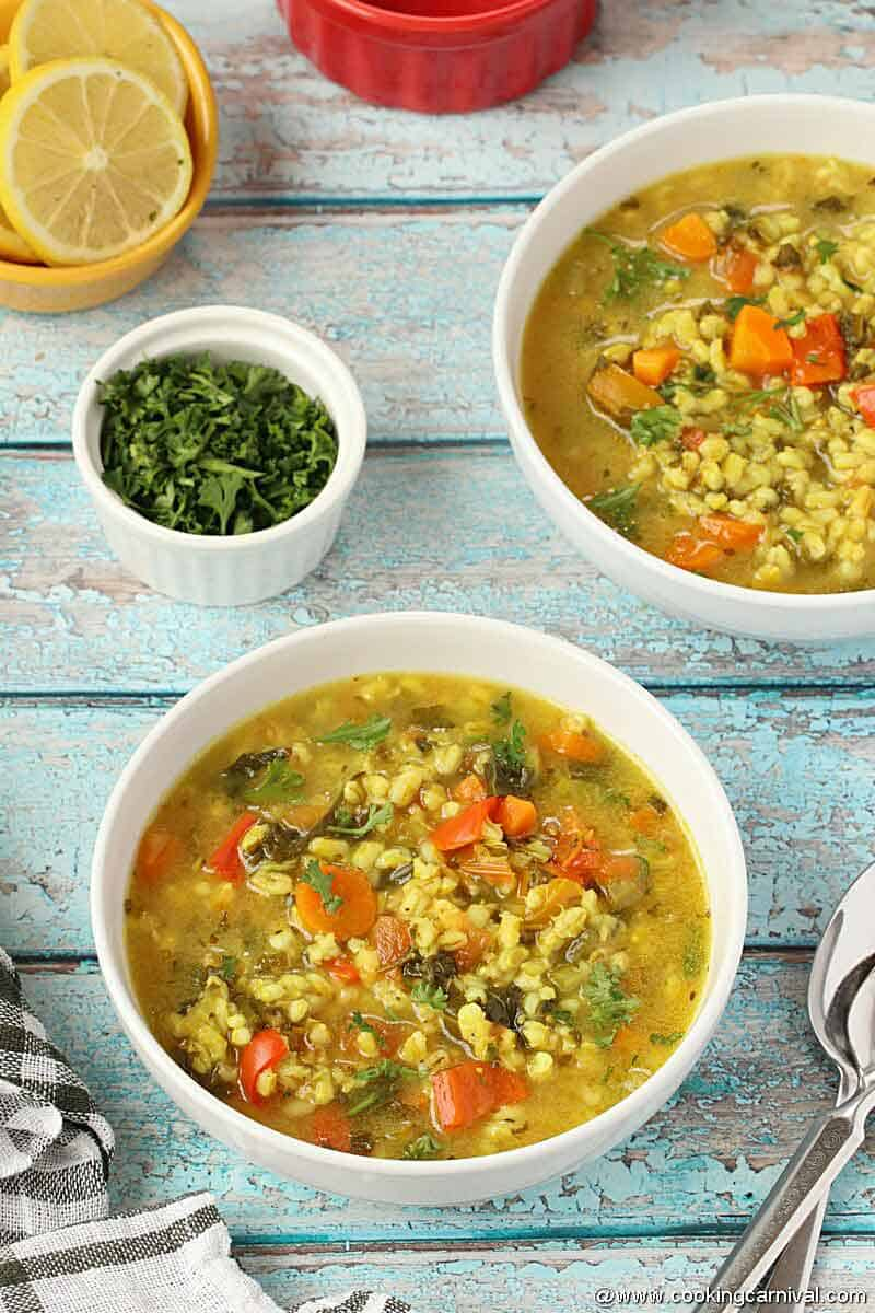 Vegetable Barley Soup in white bowl on blue rustic backdrop