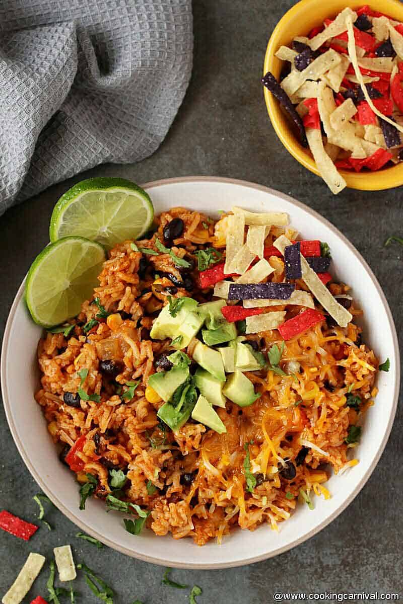 Enchilada Rice in white bowl topped with avocado, tortilla chips and lemon wedges on the sides