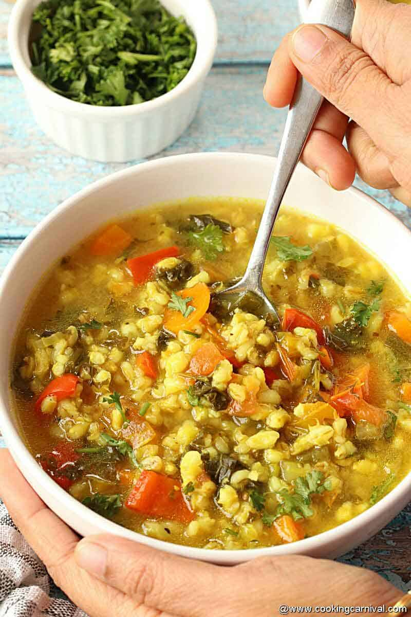 Spooning Vegetable Barley Soup from white bowl made in Instant Pot