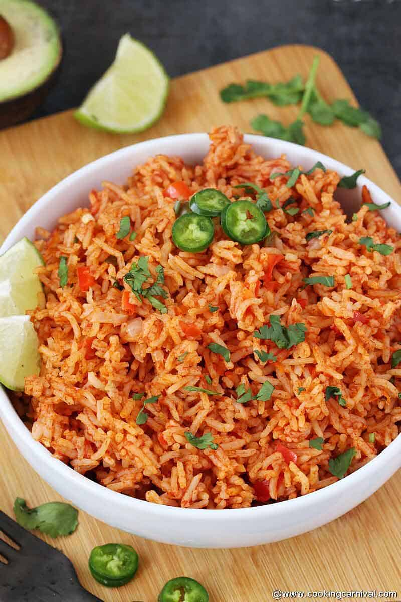 Mexican rice in white bowl with lime wedges and jalapenos