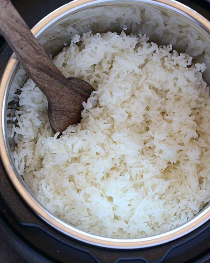 Jasmine rice in instant pot with wooden spatula