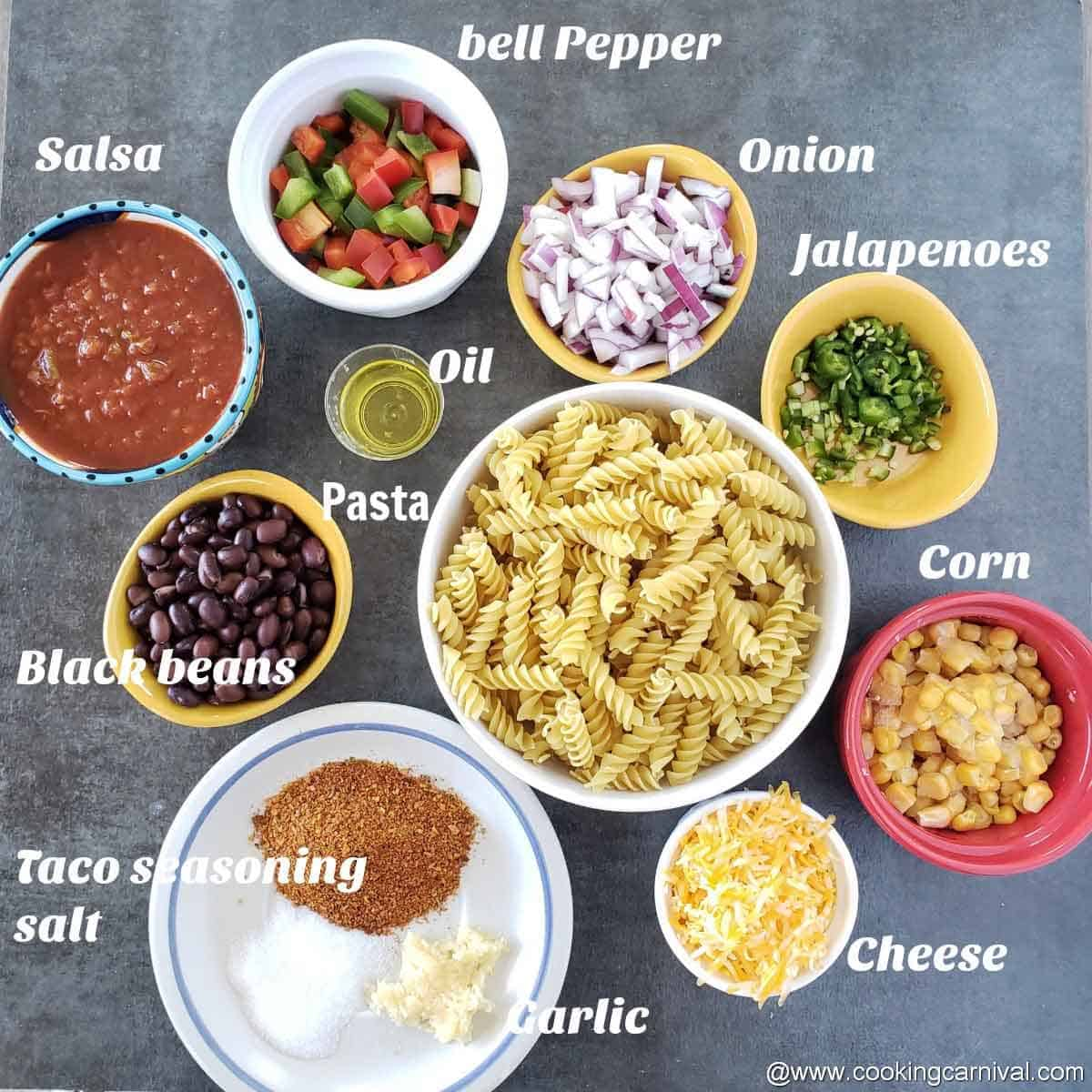 Pre-measured ingredients of pasta recipes on black tile