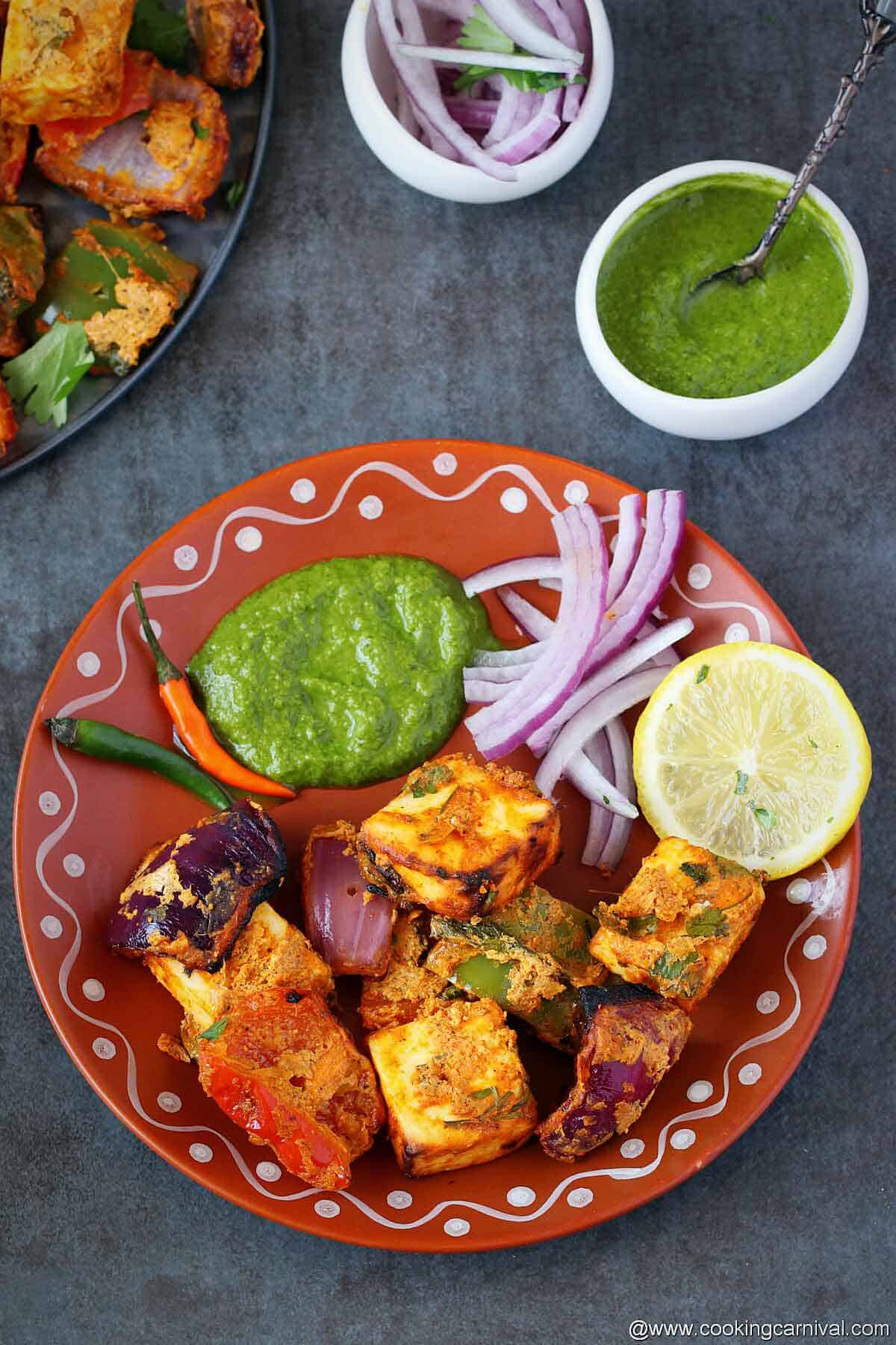 Paneer tikka served in a traditional indian plate with mint chutney, onion and lemon slices