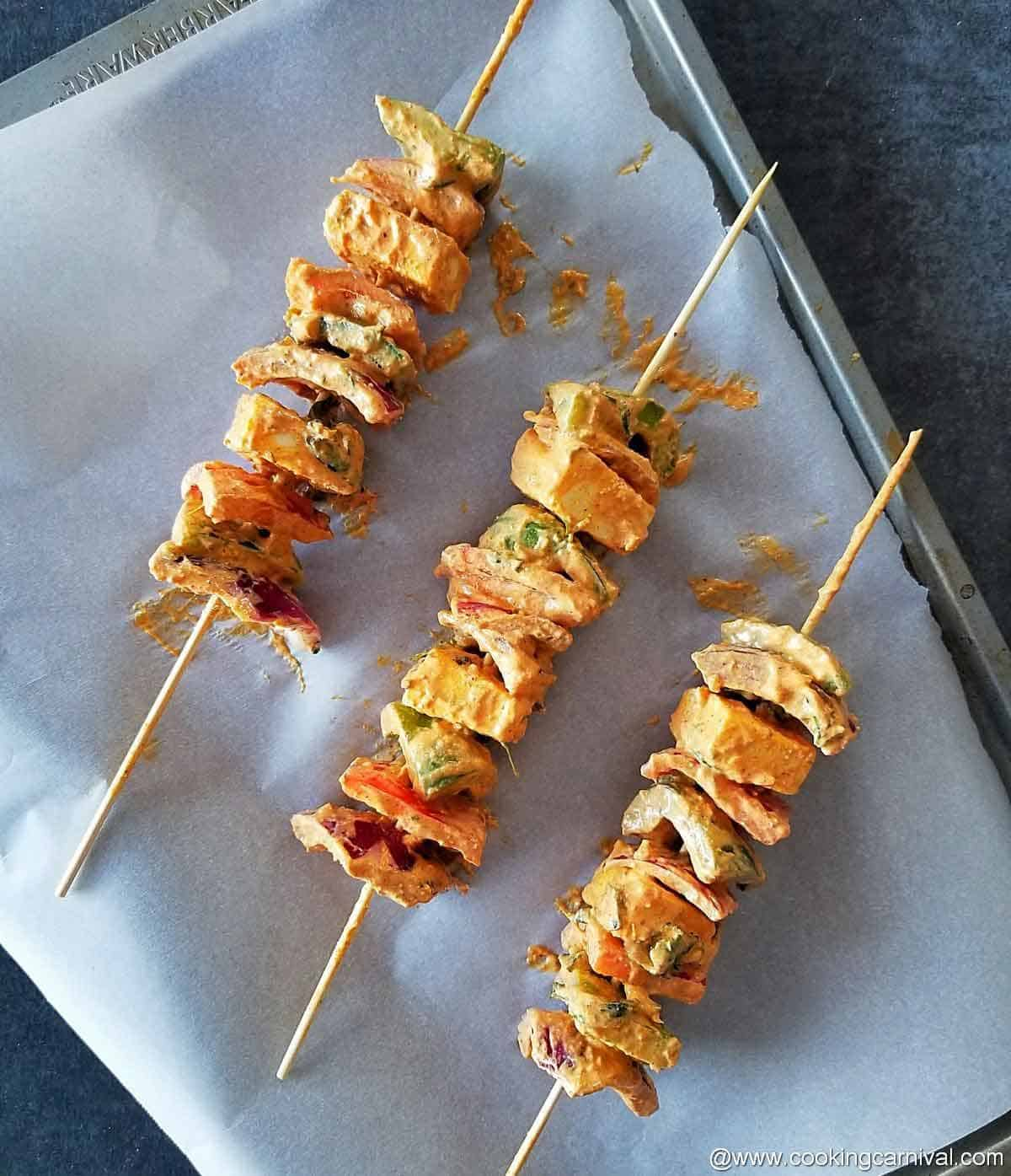 panner, pepper and onion in skewer on a baking sheet
